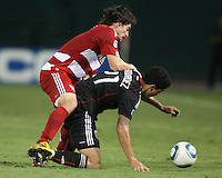Pablo Hernandez #21 of D.C. United is pinned down by Heath Pearce #4 of FC Dallas during an MLS match at RFK Stadium in Washington D.C. on August 14 2010. Dallas won 3-1.