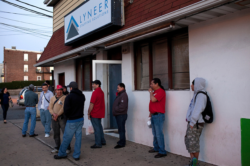 A staff member of Lyneer Staffing Solutions, left, arrives to let temp workers inside on French Street as they wait for vans to take them to warehouses surrounding New Brunswick, NJ on April 18, 2013. Across America, temp work has become a mainstay of the blue-collar economy, leading to the proliferation of ?temp towns? ? places where it's difficult to find work except through a temp agency and where workers suffer wage theft, no benefits and high injury rates, all for jobs that may end tomorrow for any reason.