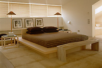 Simple wooden furniture and luxurious textures have been juxtaposed to create a bedroom of comfort and style`