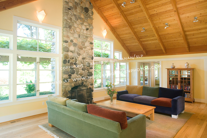 Large south and west-facing windows flood the high-ceilinged living room (LR) of this waterfront weekend vacation retreat on Washington State's Vashon Island with natural light throughout the day, while the large rock fireplace offers warmth on cold winter days.