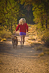 Woman and her dog running on the trail at La Pine State Park, La Pine, Oregon.