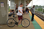 Merrick, New York, U.S. - July 14, 2014 - During evening rush hour, a man with his bicycle waits for a train to arrive on elevated platform of Merrick train station of Babylon branch, after MTA Metropolitan Transit Authority and Long Island Rail Road union talks deadlock, with potential LIRR strike looming just days ahead.