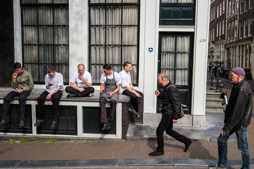 Nederland, Amsterdam, 30 mei 2015<br /> Keukenpersoneel van een restaurant heeft pauze vlak voordat de drukte van de avond begint. Ze roken nog wat en checken hun smartphones voordat het werk begint. <br /> Foto: Michiel Wijnbergh