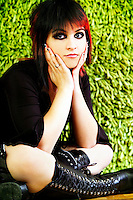 Punk rock girl with big black boots and black and red hair sitting
