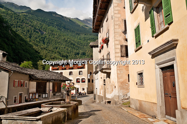 Houses and old stone fountain in a small square in the small town of Promotogno in the Swiss valley of Bregaglia in the Graubunden Canton of Switzerland
