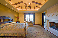 Carved king size bed in elegant bedroom with ornate fireplace and domed wood beamed ceiling and daylight in window