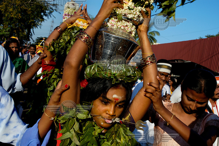 An ethnic Tamil woman carries a pot of milk as an offering along a pilgrimage trail during the annual Thaipusam festival of penance and thanksgiving.  She has a skewer piercing her tongue as a form of mortification which follows a session of fasting and prayer.  The Tamil Hindu festival commemorates the birth of Hindu Lord Murugan and his triumph over evil.  Pilgrims engage in various acts of devotion such as carrying burdens, flagellation and body piercing as they take part in a 15-kilometre procession to the Batu Caves.