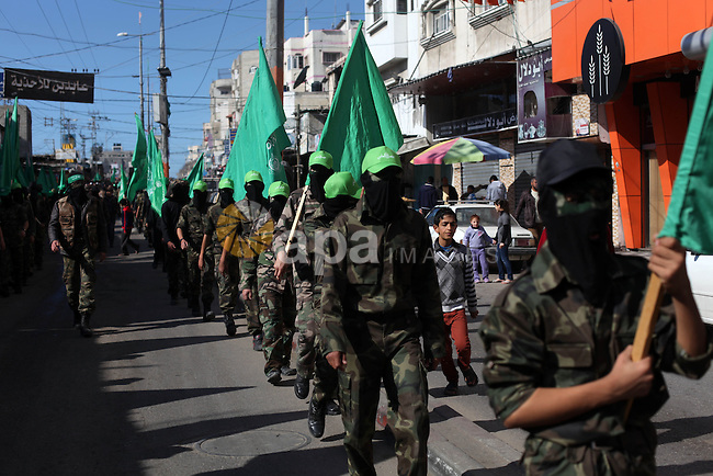"""Palestinian supporters of Hamas movement take part in a demonstration in solidarity with Palestinian refugees in the Yarmouk refugee camp in the suburbs of the Syrian capital of Damascus, in Nuseirat camp in central Gaza Strip, Jan. 24, 2014. The Yarmouk camp once housed some 160,000 Palestinian refugees from the 1948 war in Israel known by Palestinians as """"Naqba,"""" or the Catastrophe, and by Israelis as the War of Independence. The dire conditions at the Yarmouk camp are a striking example of the catastrophe unfolding in rebel-held areas blockaded by the Syrian government. Photo by Ashraf Amra"""