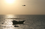 A United States Navy SH-60S Sea Hawk helicopter provides support to a visit, board, search and seizure (VBSS) team in a 7-meter rigid-hull inflatable boat, assigned to the guided-missile destroyer USS Kidd (DDG 100) in the Arabian Sea on Thursday, January 5, 2012. The VBSS team boarded the Iranian-flagged fishing dhow Al Molai after the dhow's master claimed he was being held captive by pirates. Kidd's VBSS team detained 15 suspected pirates who were reportedly holding a 13-member Iranian crew hostage for the last two months. Kidd is conducting counter-piracy and maritime security operations while deployed to the U.S. 5th Fleet area of responsibility. .Credit: U.S. Navy via CNP