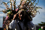 "A silletero carries flowers while she attends the traditional ""Silletero"" parade during the Flower Festival in Medellin August 7, 2012. Photo by Eduardo Munoz Alvarez / VIEW."