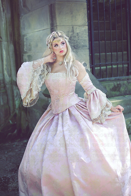 Young woman in pink period costume standing outdoors