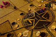 Washington, DC - April 22, 2016: A memoriam of flowers and candles in tribute to Grammy Award winning singer/song writer Prince has been setup on a sidewalk plaque in front of the Warner Theater in the District of Columbia, April 22, 2016, on the day of his death.  (Photo by Don Baxter/Media Images International)