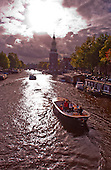 Holland, Amsterdam.  Boat heading towards the Mint Tower along a canal.  The sunshine breaking through the clouds casts a wonderful sheen onto the surface of the canal.