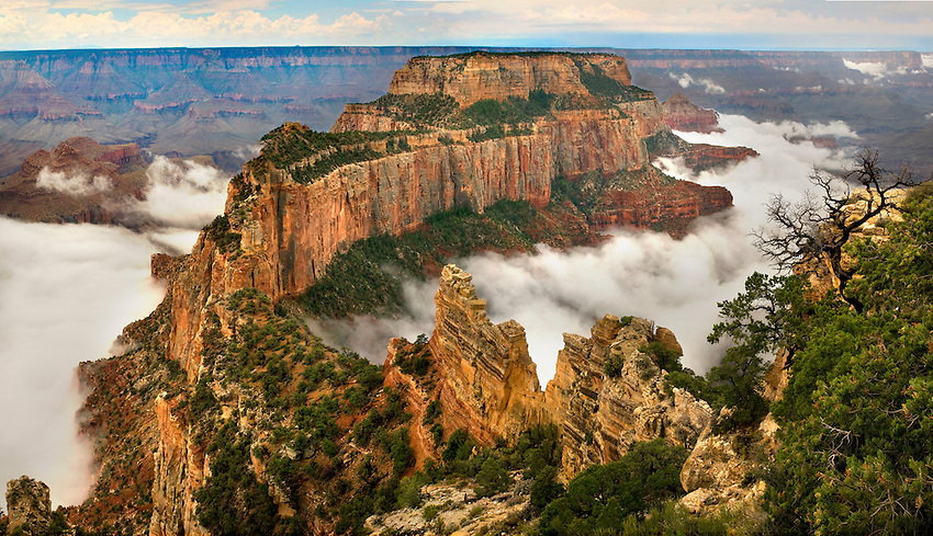 Summer monsoon storm clouds wrap around Wotans Throne below the North Rim of Grand Canyon National Park.