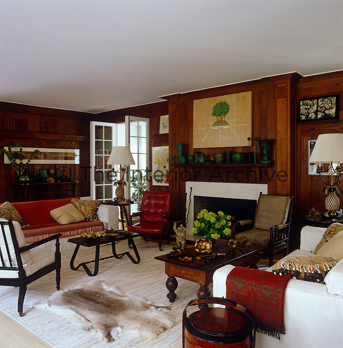 A wood panelled drawing room with a collection of vintage and antique furniture and a white and red color palette