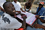Men play dominoes in Batey Bombita, a community in the southwest of the Dominican Republic whose population is composed of Haitian immigrants and their descendents. Clipping clothespins on your face keeps score of losing points.