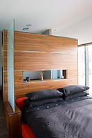 In the open-plan master bedroom the sleeping area is separated from the bathroom by a partition clad in wood panelling also serving as a headboard for the large double bed