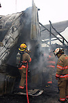 Firefighters extinguishing hot spots of flames in a collapsed building after a fire in Menomonee Falls Wisconsin