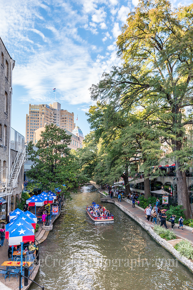 It was such a nice day along the river walk in San Antonio, you can see the river boat full of tourist and people walking and out having a meal at one of the many fine restaurants on this beautifu day with a great sky and good clouds.