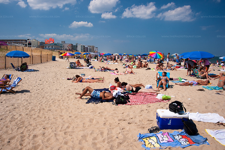 Sunbathers have more room and peace at the back of the beach, away from the crowd of kids and families that line the water on a summer day at Rehoboth Beach, Delaware, USA.