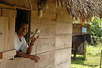 Man in his thatched-roof, wood hut in Mayan village of Midway in Southern Belixe holding the village's only phone. His donkey is out back