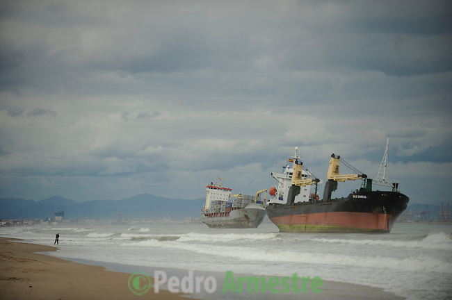 A Spanish Coast Guard patrol boat and an helicopter attempt to rescue two cargo ships that ran aground at Saler beach near Valencia on September 29, 2012 after a heavy storm. At least eight people, including a young girl and an elderly woman, have died in Spain as a result of floods brought on by downpours, regional officials said. Four people died in the Andalusia region, including a woman in her 80s, a couple found in their car and a man who died of a heart attack. Some 500 people remained evacuated from their homes in the area early on Saturday after the torrential rains caused rivers to break their banks and flooded roads and railways, regional authorities said. (c)Pedro ARMESTRE