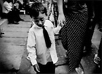 Young boy walking hand in hand with his mother on a central Yangon street,  Burma.