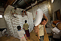 The sugar is preserved in a storage room inside gunnysacks piled up to the ceiling.