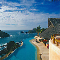 An azure blue horizon pool follows the contours of the hill and has views out over the Pacific Ocean