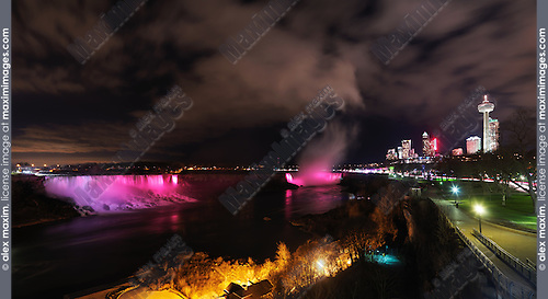 Nighttime panoramic scenery of Niagara Falls illuminated with colorful lights. Ontario, Canada.