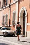A woman in a sun dress walks down a street in Ravenna, Italy.