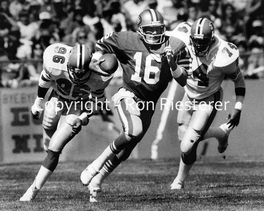 San Francisco 49er quarterback Joe Montana scrambles away from a duo of Falcon linemen. (1985.photo by Ron Riesterer)