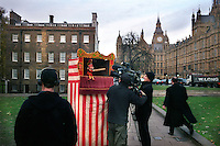 UK. London. From a story on Abingdon Street Gardens, a small patch of land, often referred to as College Green, that lies next to The Houses of Parliament in Westminster. It is a place where the media and the politicians come face to face. Interviews are held, photo shoots are set up and bewildered tourists stroll by..Photo shows a TV crew that has set up a Punch & Judy show after a reference to 'Punch & Judy politics' was made in The House of Commons..Photo©Steve Forrest/Workers Photos