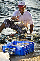 A smiling local fisherman is cleaning the net and throwing the fish into the plastic box