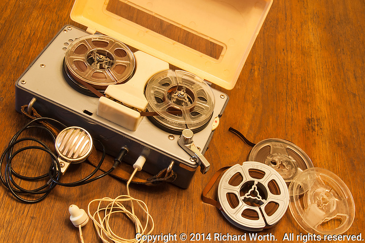 An antique toy tape recorder from the 1950s or 60s with lapel microphone, earphone and reels of magnetic recording tape.