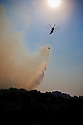 Fire service helicopter drops water over a forest fire burning near Ancient Olympia; smoke from the fires blocking out the sun turning the sky into a dark orange haze; Peloponnese, Greece, 2007;