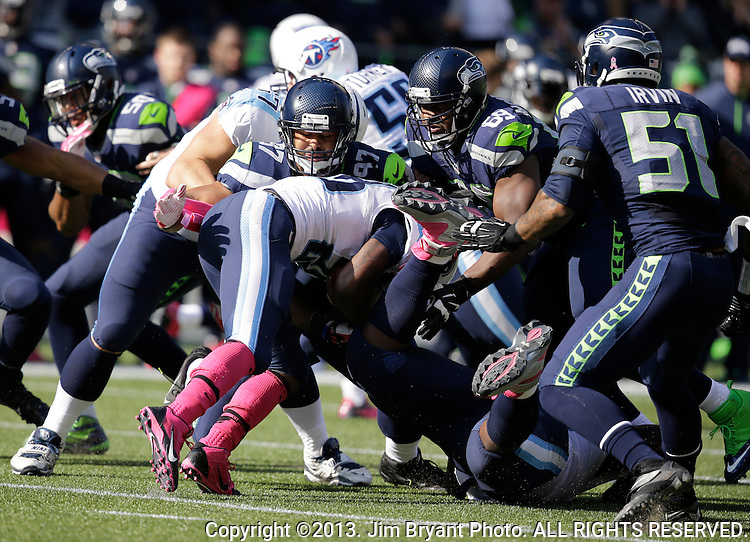Seattle Seahawks defenders Red Bryant, (97),  Clinton McDonald, and Bruce Irvin (51)stops Tennessee Titians running back Chris Johnson (28) at CenturyLink Field in Seattle, Washington on  October 13, 2013. The Seattle Seahawks beat the Titians  20-13.   ©2013. Jim Bryant Photo. All Rights Reserved.