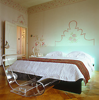 Double bed with opaque glass headboard and a Perspex chair at its foot in a room decorated with floral stencils