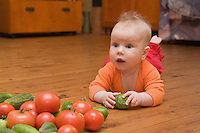 Five month old caucasian baby on wooden floor and holding pickle. Floorboard. Vegetables.