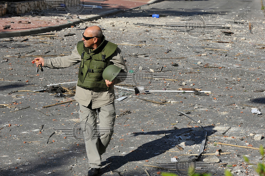 A security officer at the scene where a missile, which was shot by Palestinian militants from Gaza, had hit a building in Ashdod. Israeli forces began an air offensive against Hamas in the Gaza Strip on 27/12/2008, which quickly escalated into an offensive by land, sea and air, in retaliation against Palestinian rockets fired into Israel. After eight days of bombardment, leaving over 400 Palestinians and four Israelis dead, Israeli tanks entered Gaza on 04/01/2009...