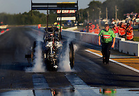 Aug. 16, 2013; Brainerd, MN, USA: A crew member looks on as NHRA top fuel dragster driver Terry McMillen does a burnout during qualifying for the Lucas Oil Nationals at Brainerd International Raceway. Mandatory Credit: Mark J. Rebilas-