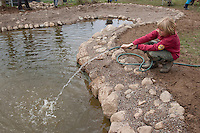 Grundschulklasse, Schulklasse legt einen Schulteich, Schul-Teich, Gartenteich, Garten-Teich im Schulgarten an, Kinder füllen Wasser mit dem Wasserschlauch in den neu angelegten Teich