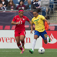 Brazilian player Marta (10) dribbles as Canadian midfielder Desiree Scott (11) defends. In an international friendly, Canada defeated Brasil, 2-1, at Gillette Stadium on March 24, 2012.