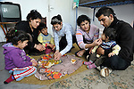 A Roma family displaced by a severe cold spell eats a meal in their temporary shelter at the Red Cross in Smederevo, Serbia. Church World Service has provided this and other affected families with food and other emergency supplies. In the photo are (left to right) Gabriela Iseni, 4; Juntena Iseni; Dzustin Stoyanovic, 6; Dzulvidana Iseni; Mirsena Iseni; Elvis Ismailov; and Elmedina Ismailov, 10 months.