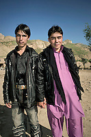 Two young men stand together holding hands, a traditional gesture of friendship in Afghanistan.