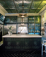 In the kitchen white subway-tiles, glass fronted cabinets, a marble topped island and a stunning glass ceiling create a glamorously retro atmosphere