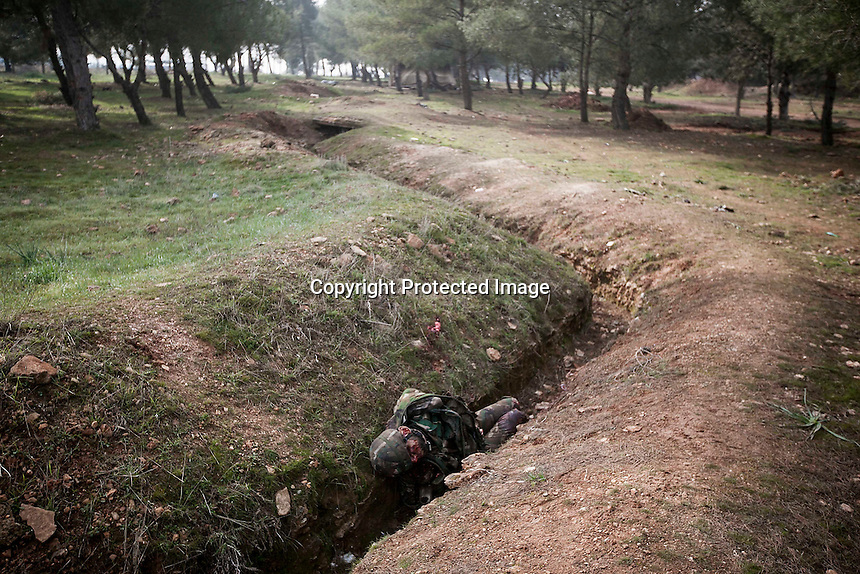 In this Sunday, Dec. 16, 2012 photo, a lifeless body of a Syrian army soldier remains laying in a trench after it was died during heavy clashes inside one militar academy besieged by rebels at the north of Aleppo, Syria. The Free Syrian Army took control over the Academy after several hours battling the troops loyal to President Bashar al-Assad. Among the casualities are one FSA General and one Syrian journalist. (AP Photo/Narciso Contreras)