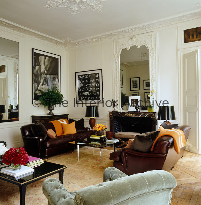 Masculine leather-covered sofas set the tone in this white painted drawing room with original ornamental plasterwork