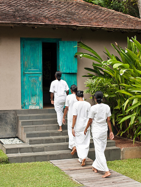 A group of female spa therapists walk to a spa treatment room at Sahana Spa, Aturuwella, Bentota, Sri Lanka.