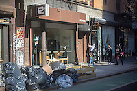 Coffee shop, uncollected trash, and other stores in the gritty but hip Lower East Side neighborhood of New York on Sunday, February 17, 2013.  (© Richard B. Levine)